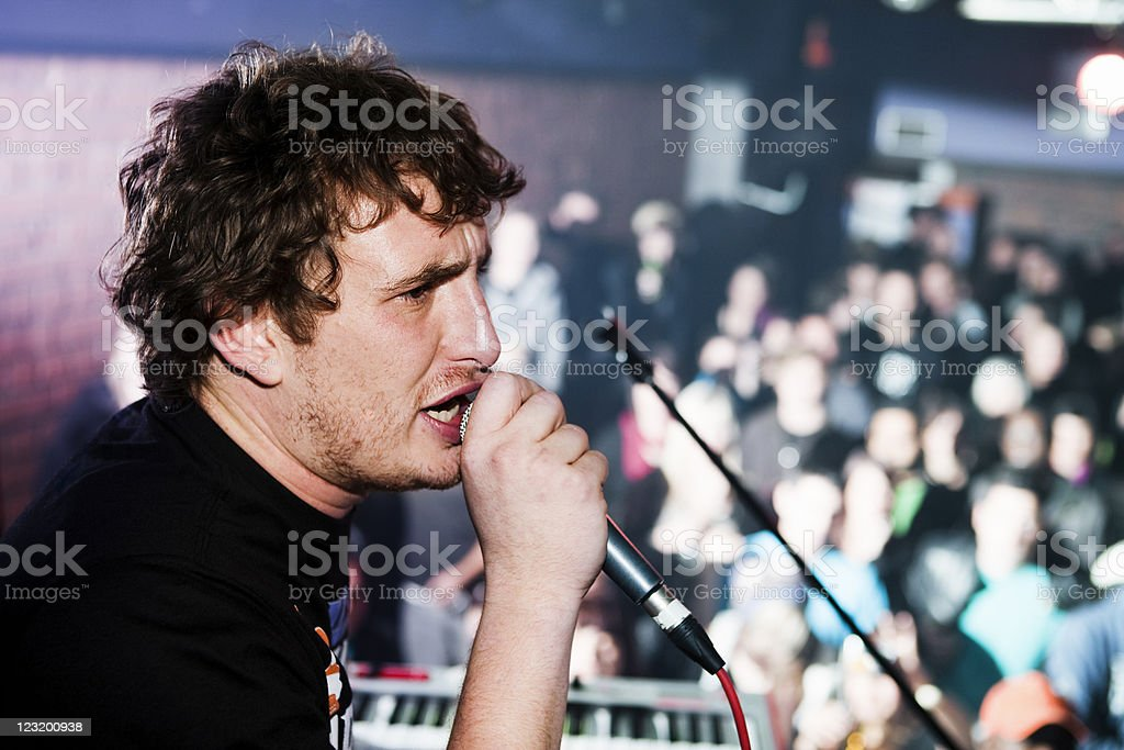 Intense young speaker or singer with audience stock photo