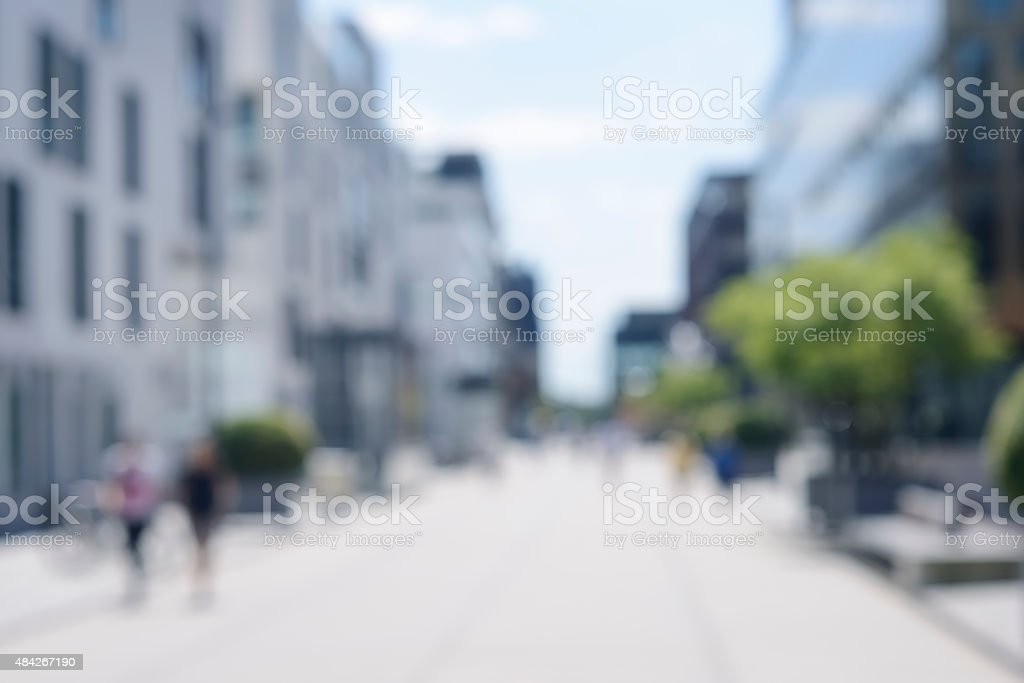 Intentionally defocused urban street with modern houses and pedestrians stock photo