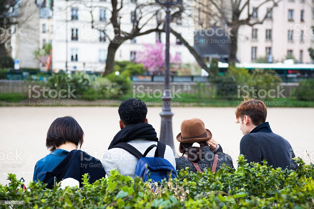 interacial group of young friends sit in Paris park stock photo