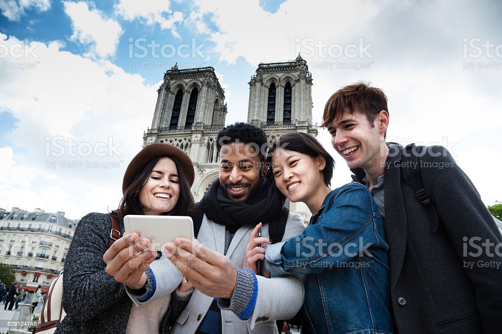 interacial group young friends take selfie at Notre Dame Paris stock photo