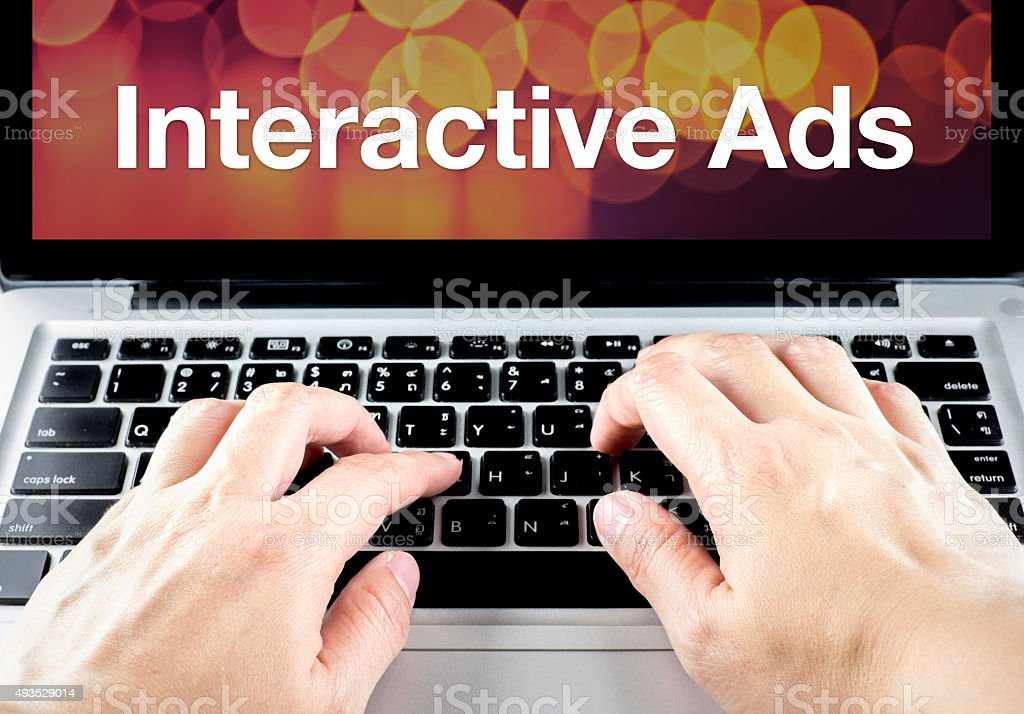 Interactive ads word on laptop screen with hand type stock photo