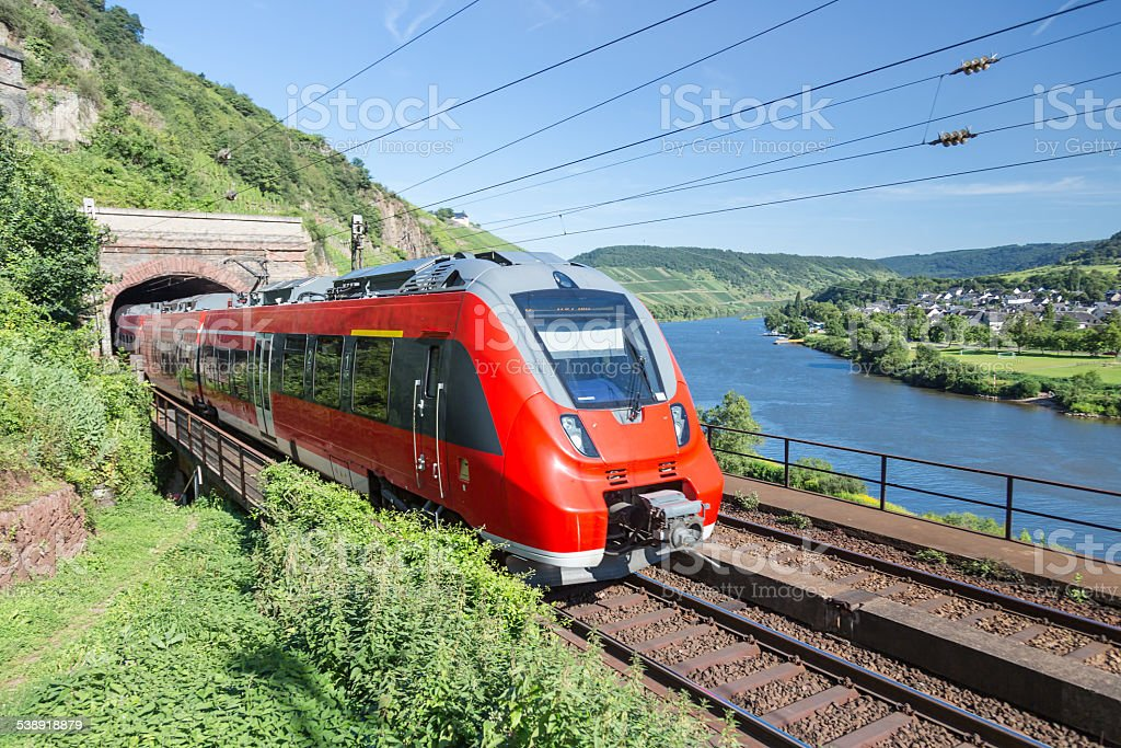 Intercity train leaving a tunnel near river Moselle in Germany stock photo