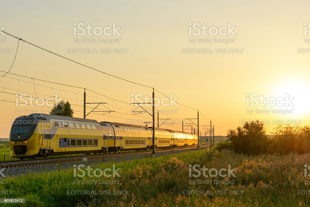 Intercity train of the Dutch Railways driving past during sunset stock photo