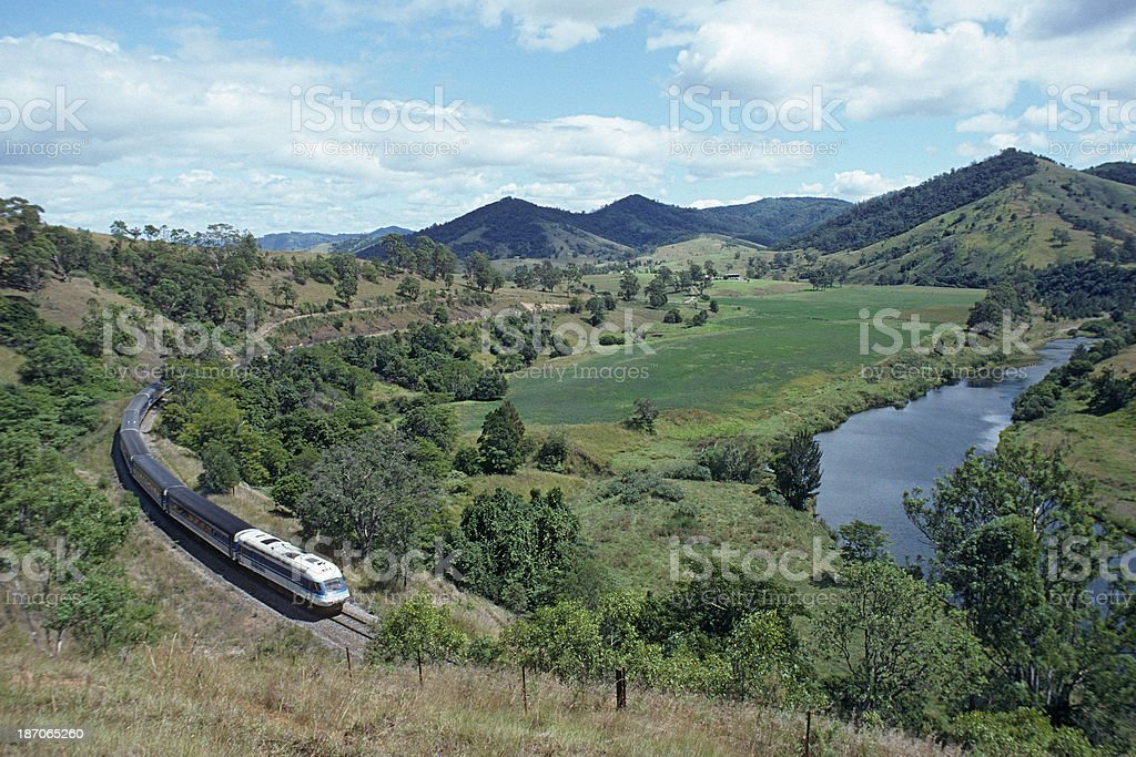 Intercity train winding through river landscape stock photo