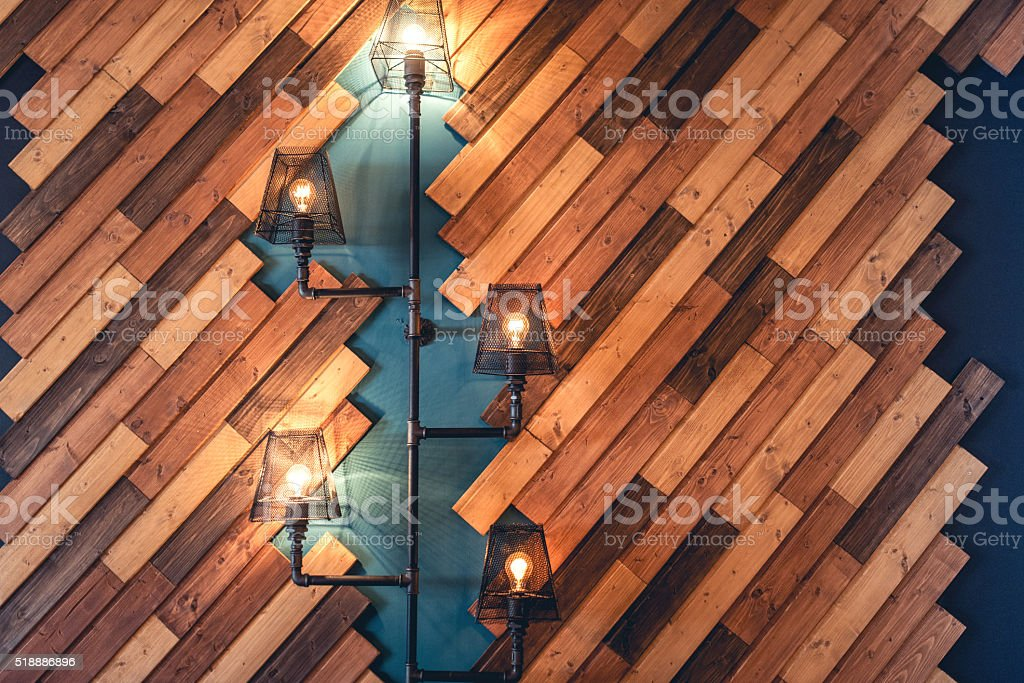 Interior design with lamps and bulb lights. Wooden wall decoration stock photo