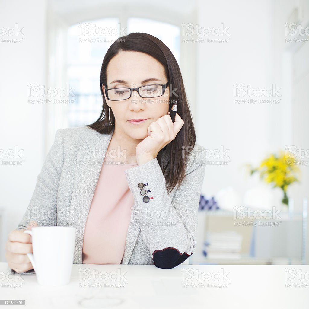 Interior designer looking at her sketches with cup of coffee. stock photo