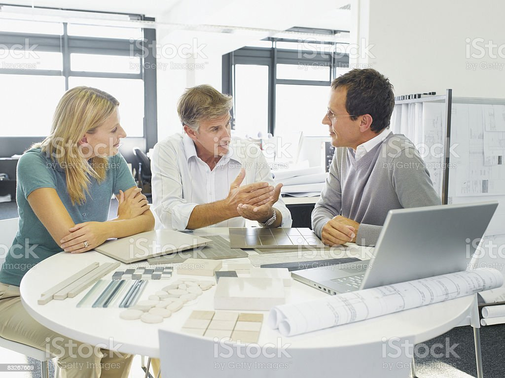 Interior designer talking with couple in showroom royalty-free stock photo