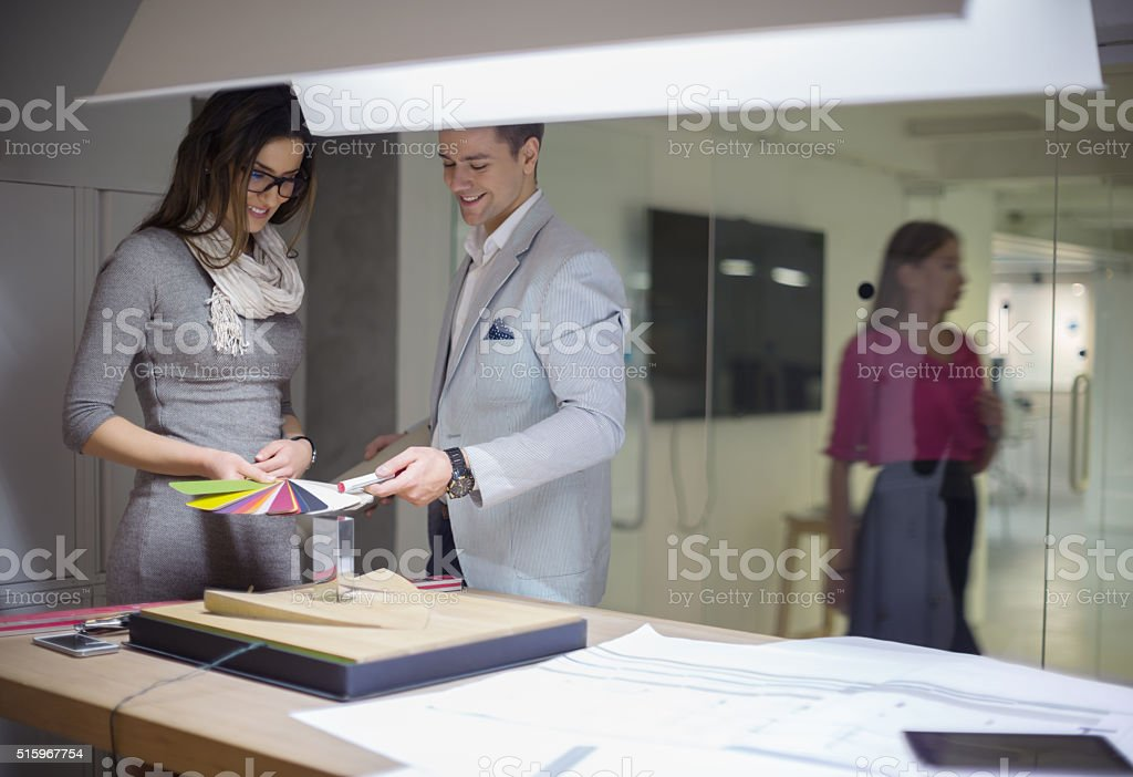 Interior designers choosing color from color swatches stock photo