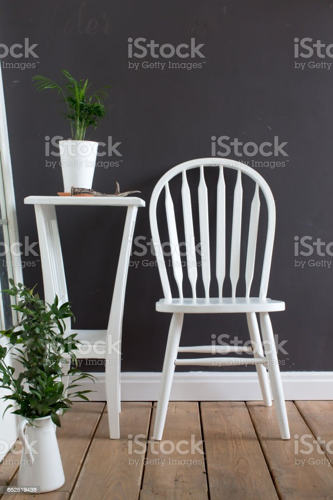 Interior furnished with chair, table with flowers stock photo
