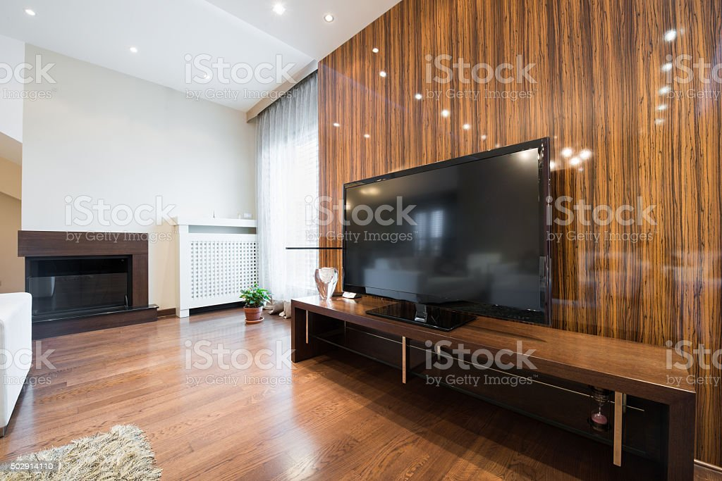 Interior of a modern living room with shiny wooden wall stock photo