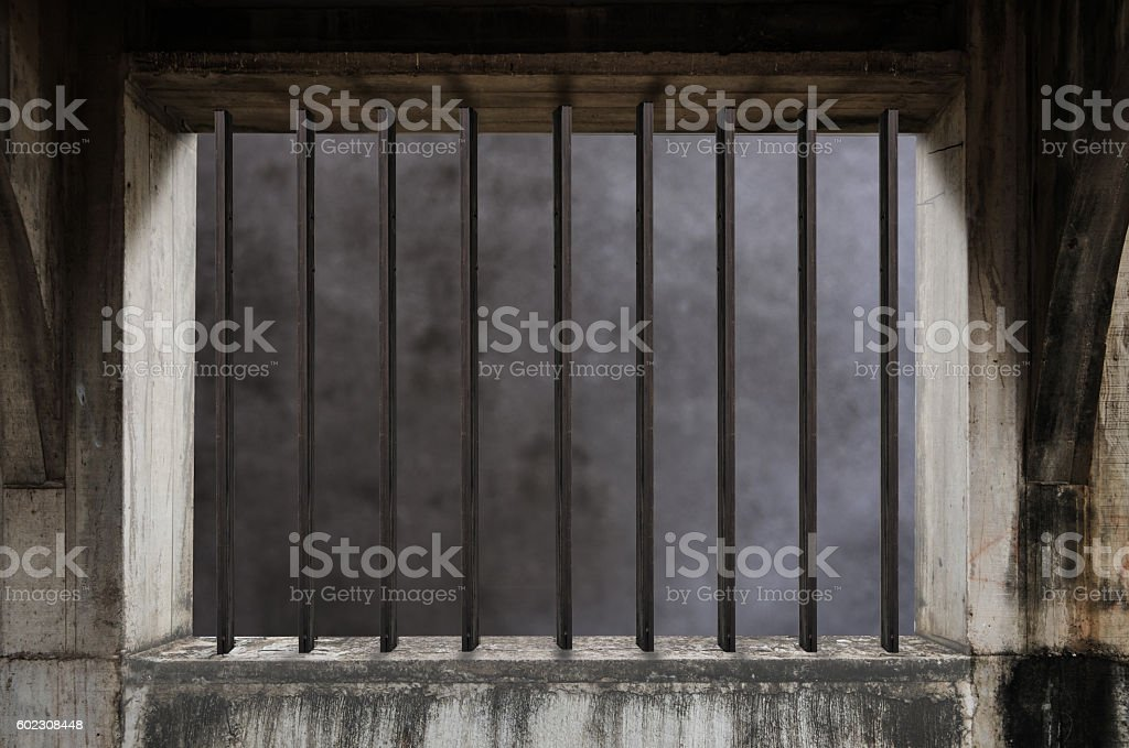 Interior of a prison cell with light shining through barred stock photo