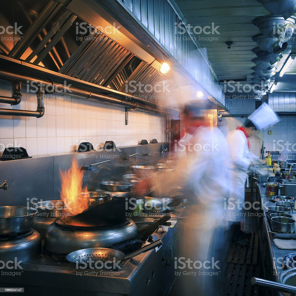 Interior of a restaurant kitchen with busy chefs stock photo