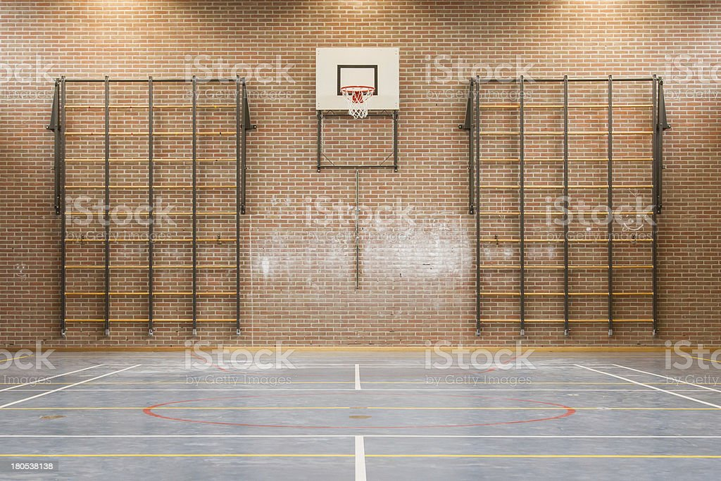 Interior of a school gymnasium with a basketball hoop stock photo