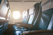 Interior of airplane with empty seats and sunlight at the