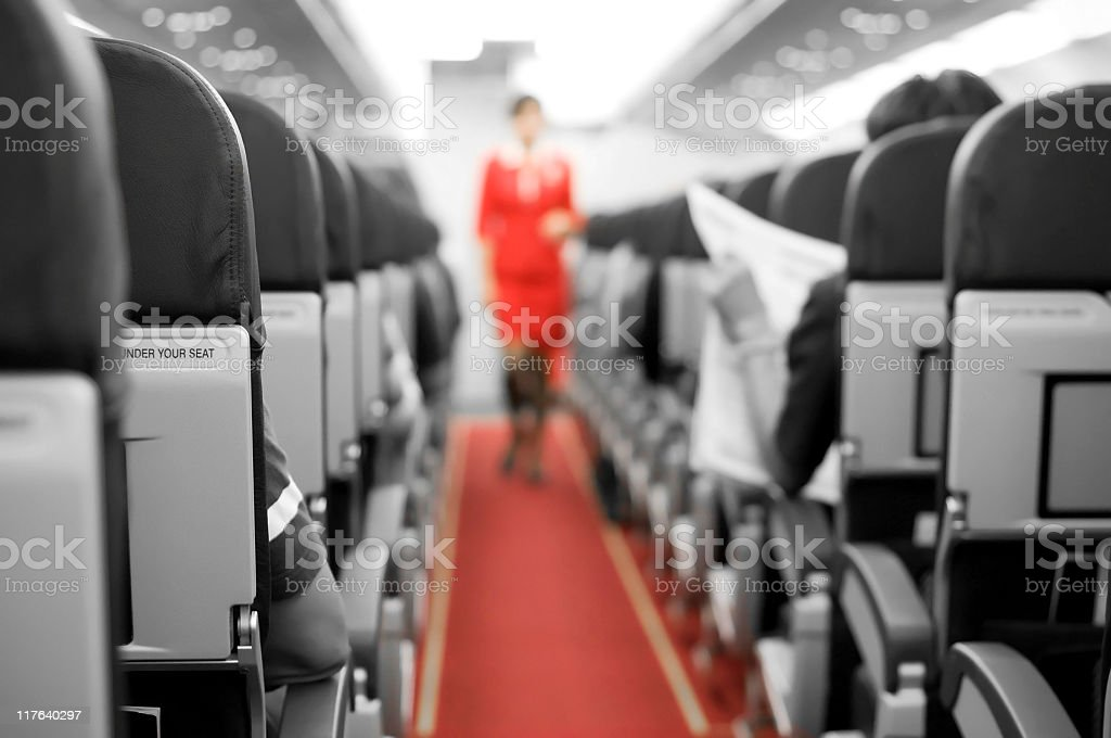 Interior of an airplane with cabin crew in the background stock photo