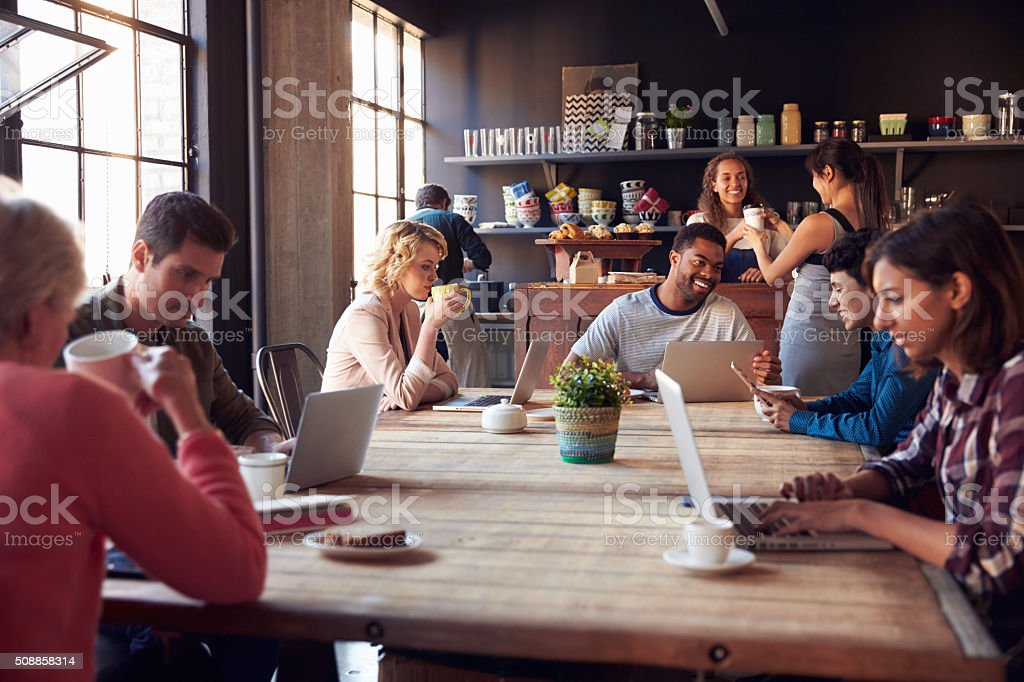 Interior Of Coffee Shop With Customers Using Digital Devices stock photo