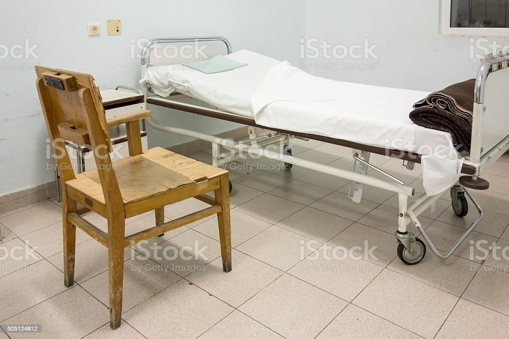 Interior of hospital room with bed and old chair stock photo