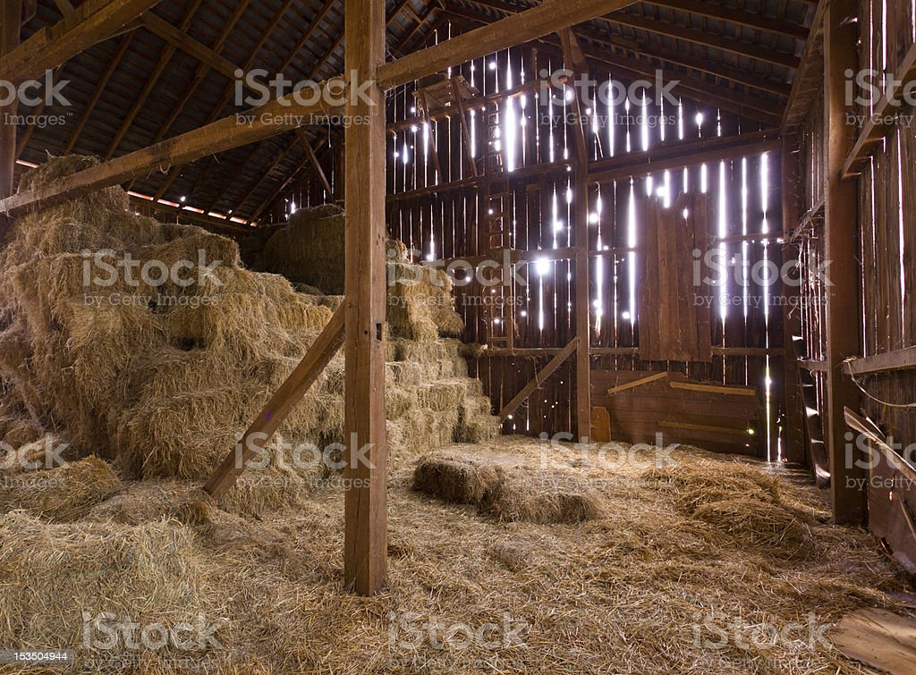 Interior of old barn with straw bales stock photo