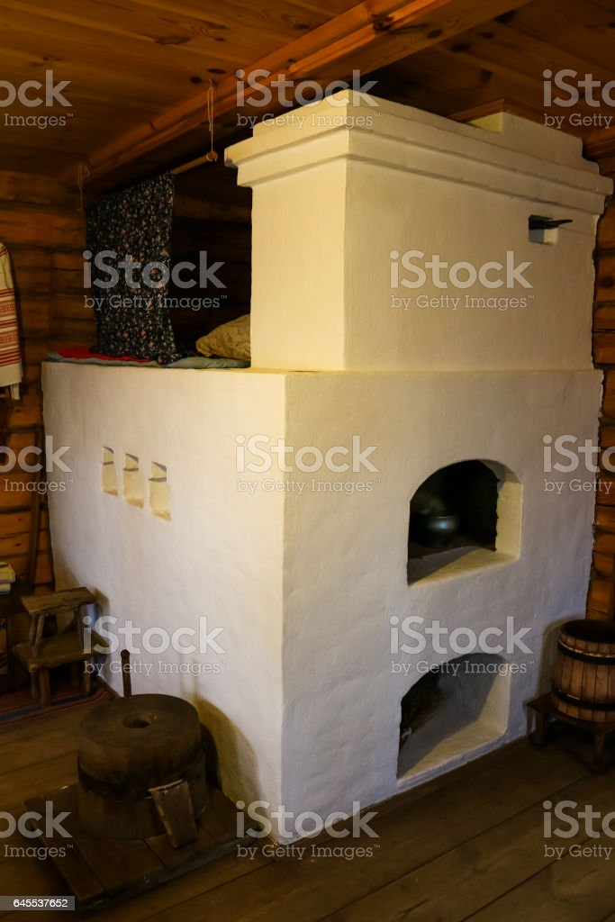 Interior of the old hut with a big white Russian stove close stock photo