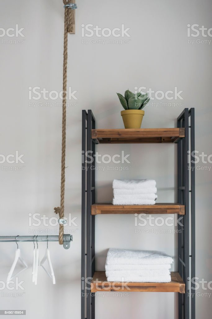 Interior of trendy hotel room with towel closet and clothes hangers on iron tube. stock photo