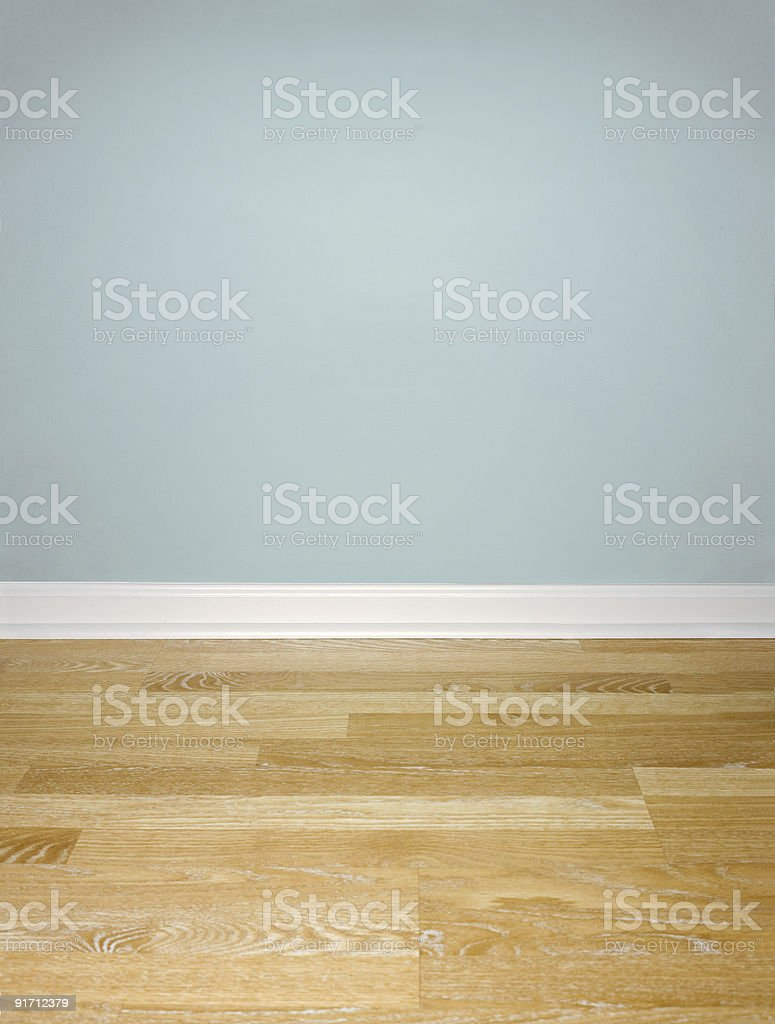 Interior of Wood Floor with White Baseboard and Blue Wall stock photo