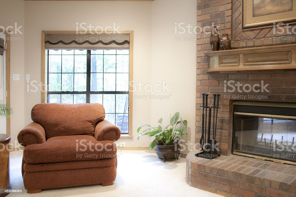 Interiors: Cozy chair by fireplace in family room. royalty-free stock photo