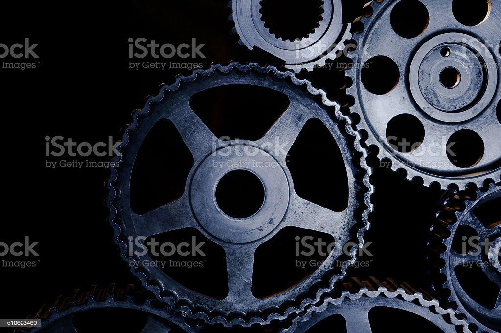Interlocking industrial  cogwheels top view on black background stock photo