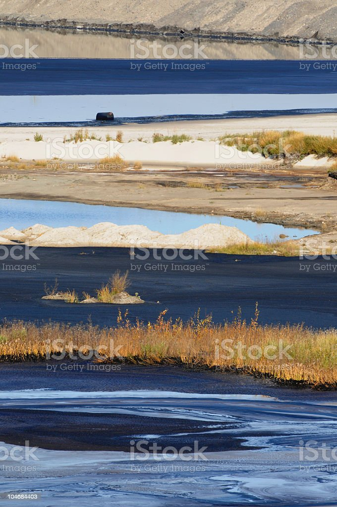 Intermittent stripes of water, oil and soil stock photo