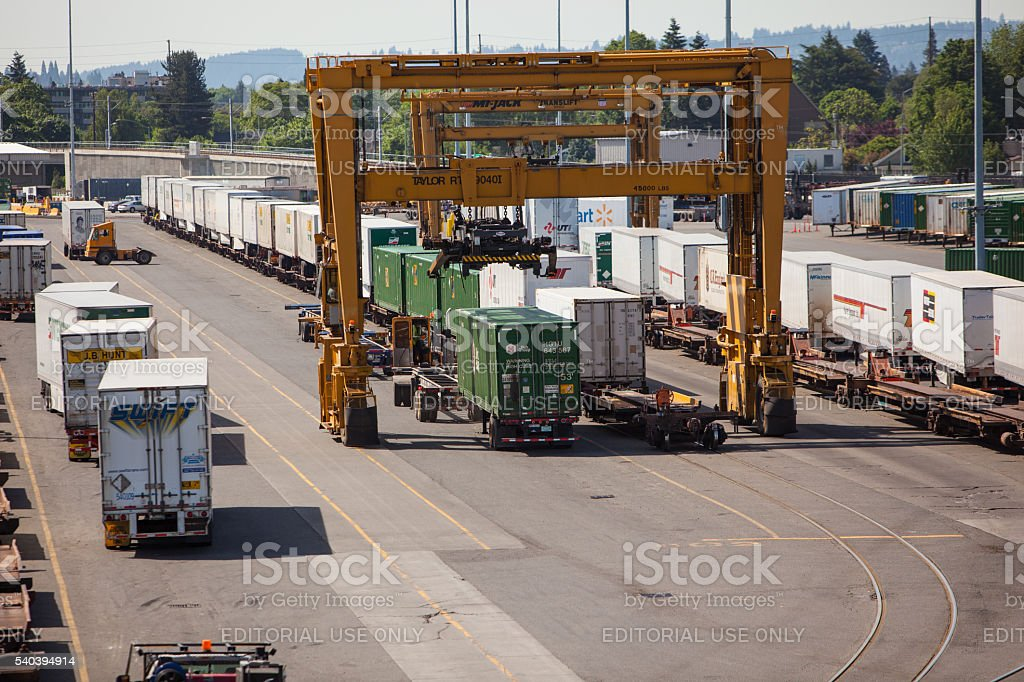Intermodal containers being transferred from railcar to trailer. stock photo