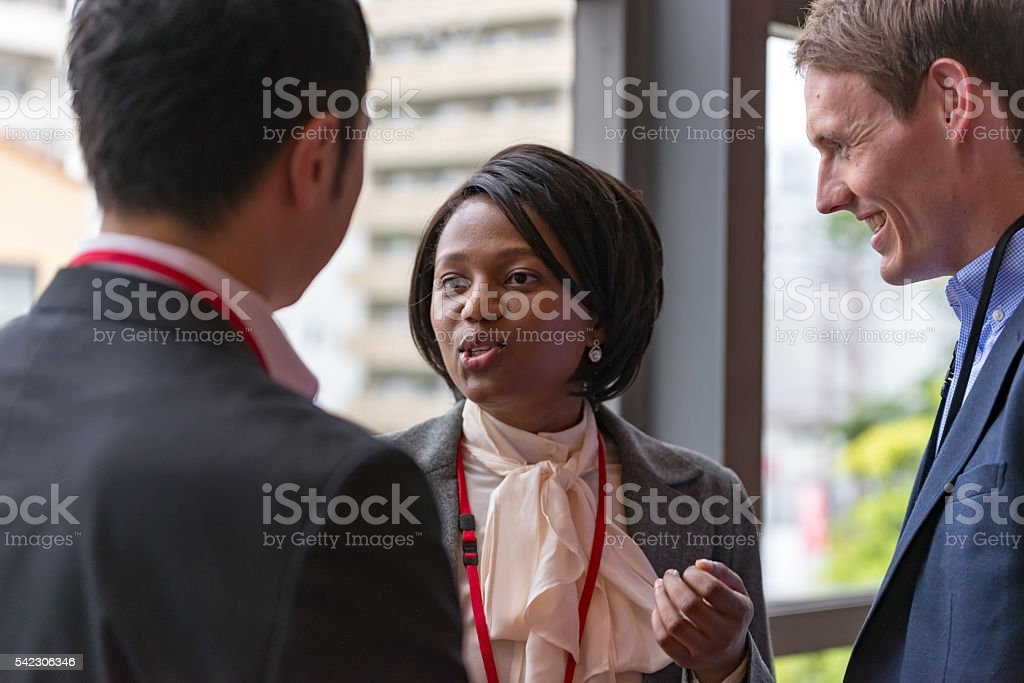 International businesspeople are talking at hallway of office building stock photo