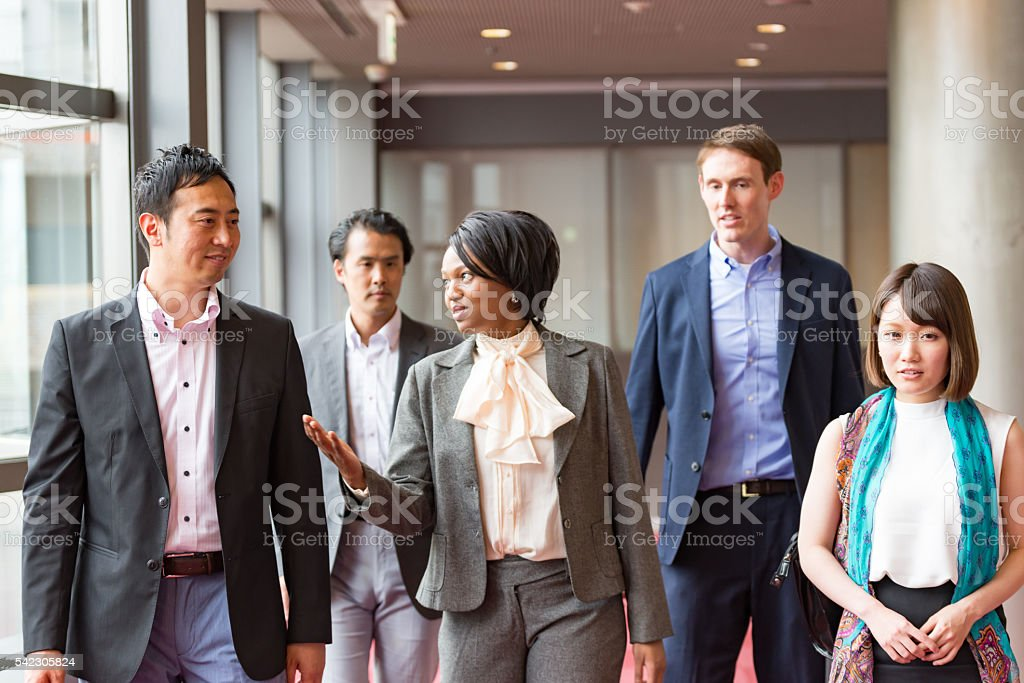 International businesspeople are walking together at hallway of office building stock photo