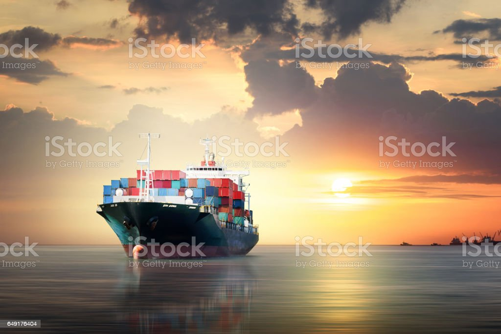 International Container Cargo ship in the ocean as sunset sky,...