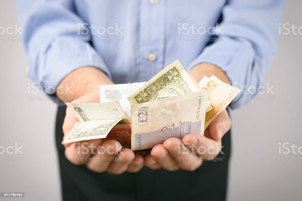 International Currency Bank Notes in Cupped Hands stock photo