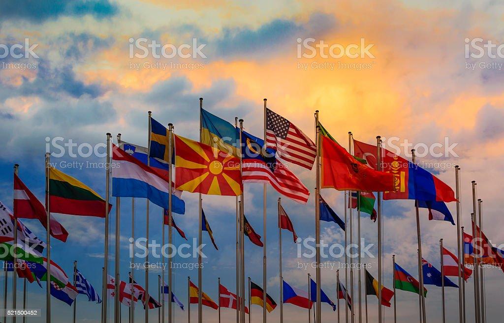 International flags against sunset sky stock photo