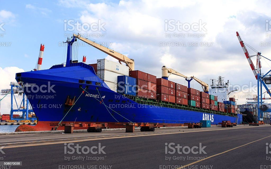 International Mega Container ship unloading containers on service trucks stock photo