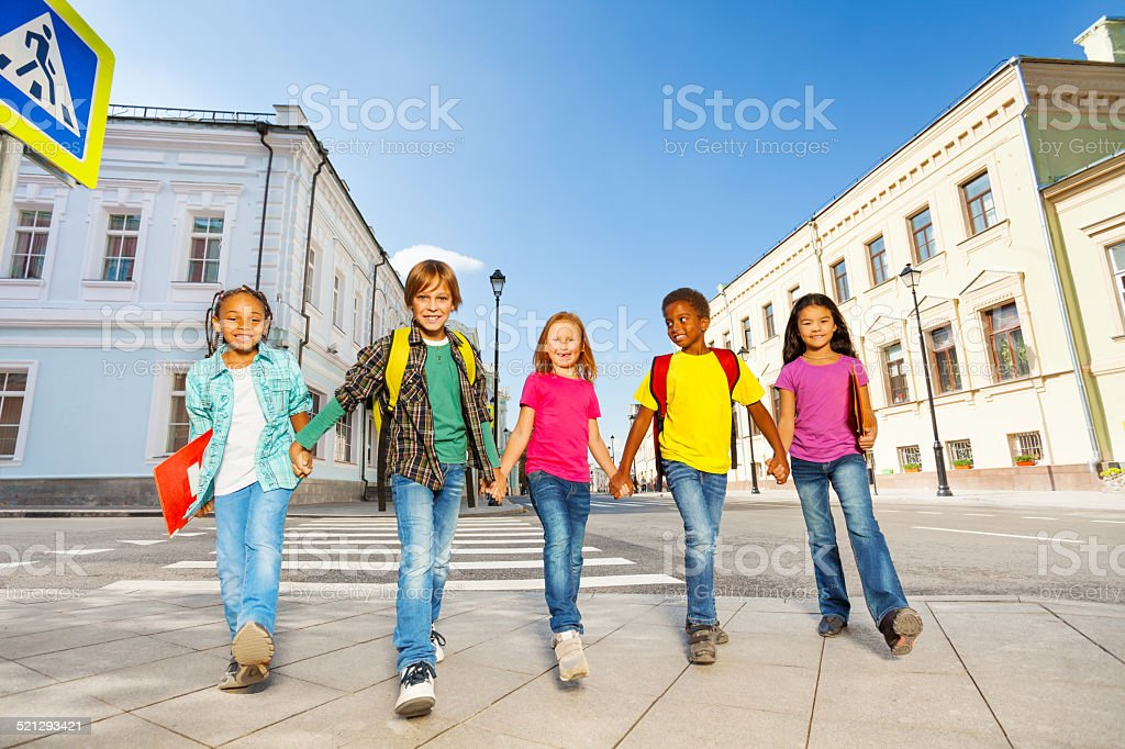 International schoolchildren walk and hold hands stock photo