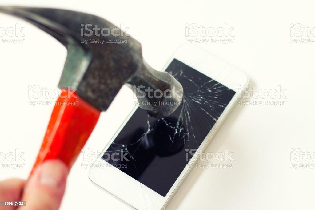 Internet Burnout: Hammer Shattering Smart Phone Screen stock photo