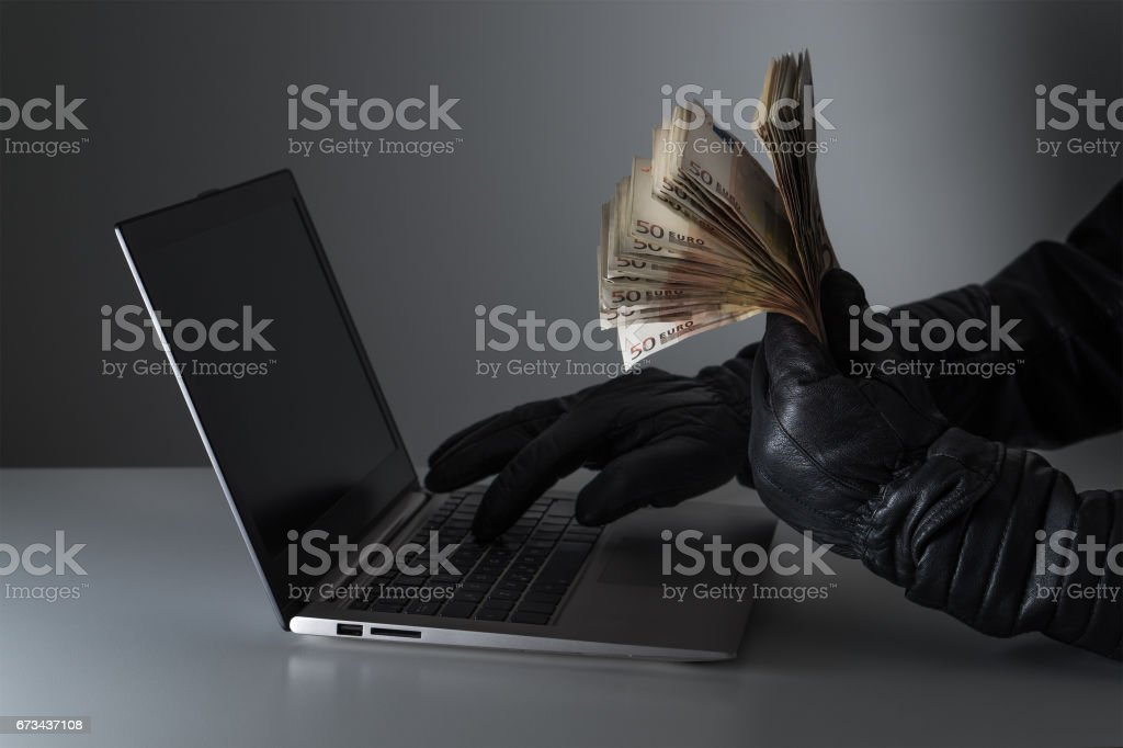 Internet fraud and cyber security concept. Criminal holding a lot of money and using laptop with black leather gloves. stock photo