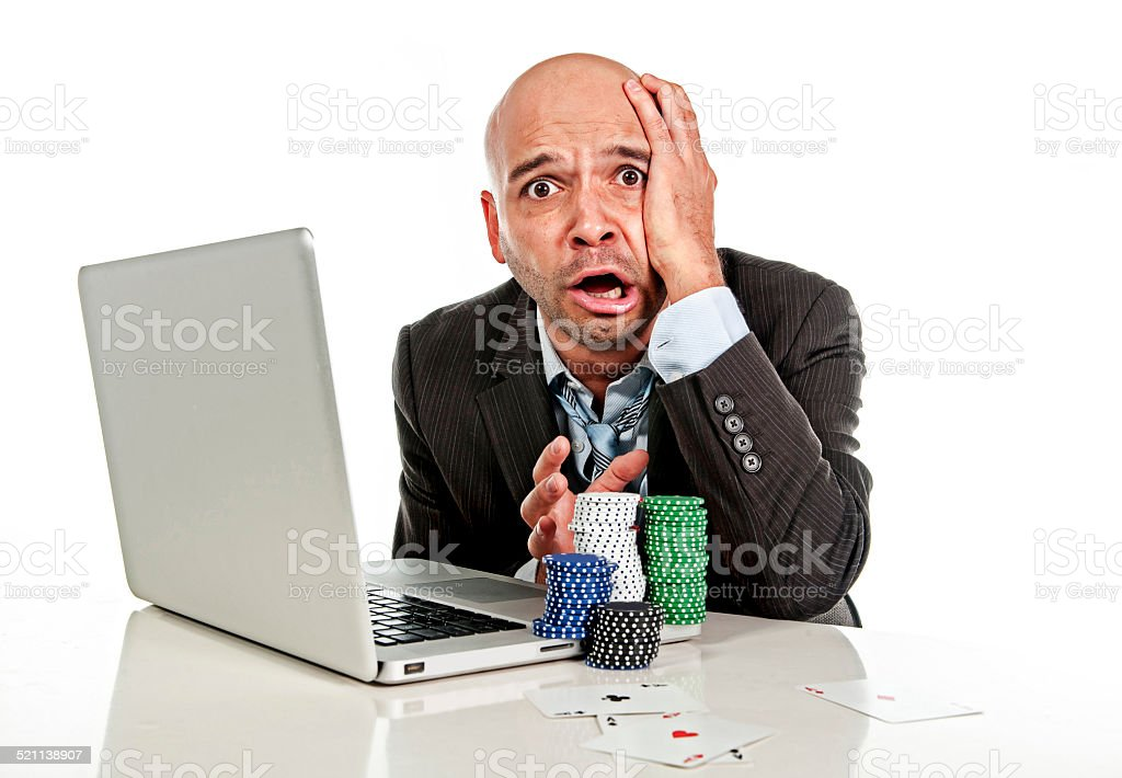 internet gambling addict businessman on computer loosing money on poker stock photo