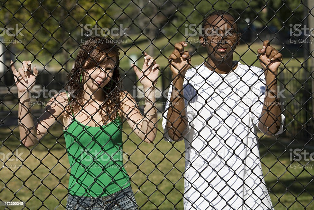 Interracial couple behind fence royalty-free stock photo