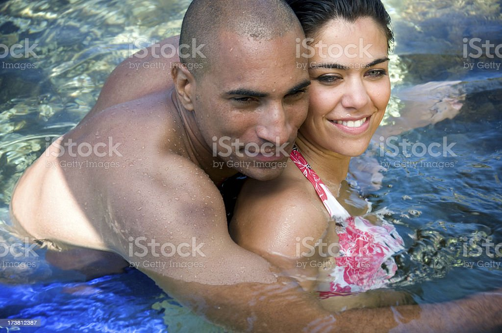Interracial Couple Cuddling in the pool stock photo
