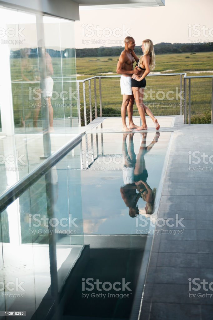 Interracial couple embracing on terrace royalty-free stock photo
