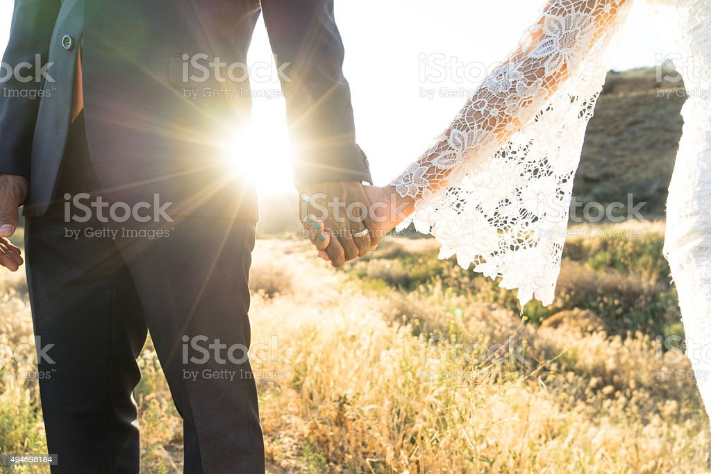 Interracial couple holding hands at wedding stock photo