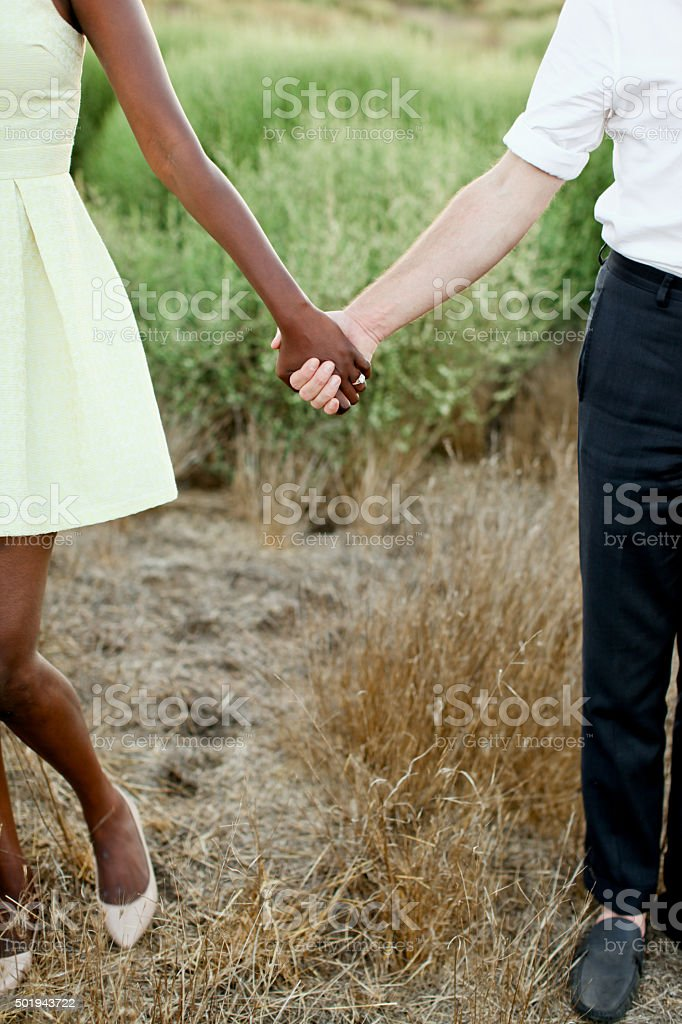 interracial couple holding hands stock photo