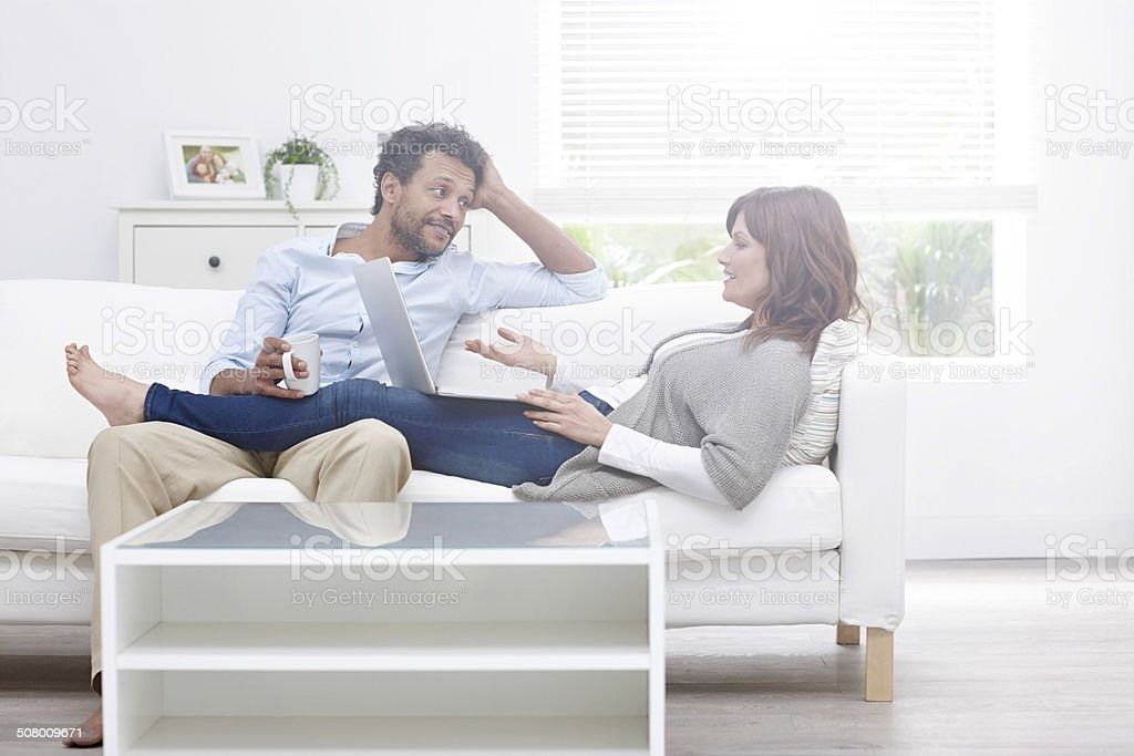 Interracial couple relaxing on sofa in free time stock photo