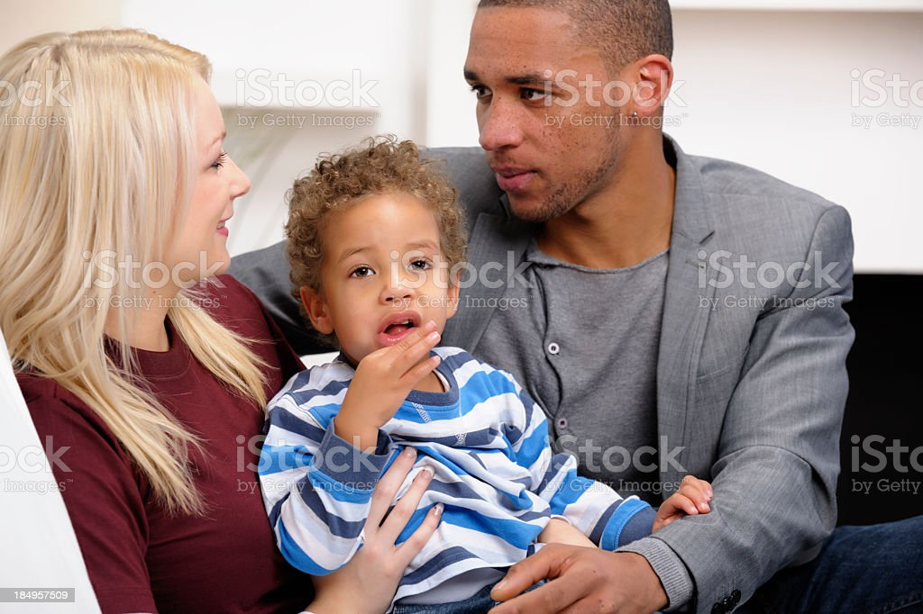 Interracial Couple Sharing Intimate Moment While Holding Toddler stock photo