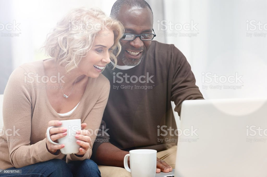 Interracial couple using laptop at home stock photo