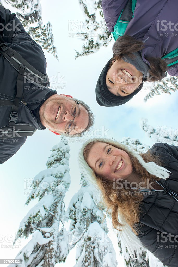 Interracial Family and Friends Looking Down, Snow Covered Tree Background stock photo