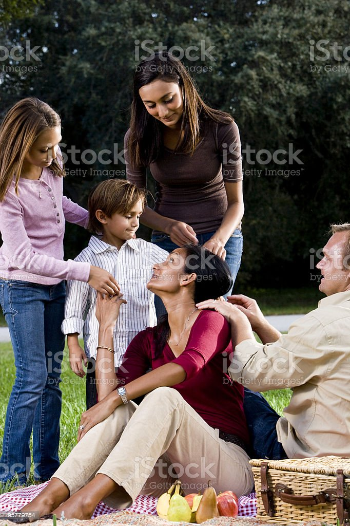 Interracial familia de cinco tener un picnic en el parque foto de stock libre de derechos