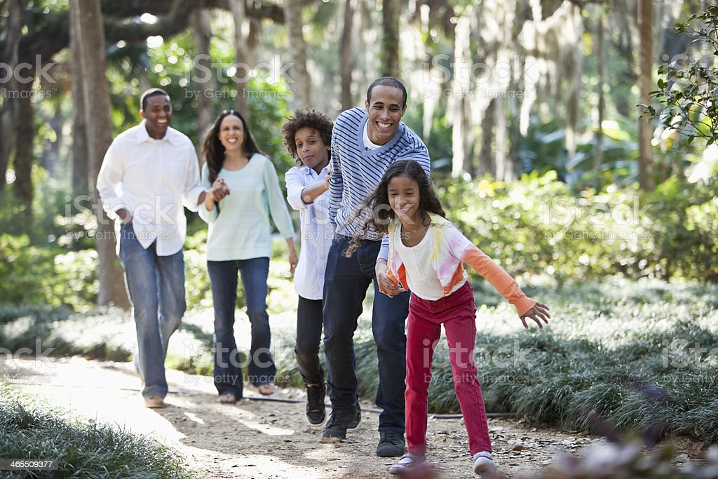 Interracial family walking in park royalty-free stock photo